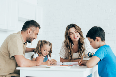 Eltern helfen Kindern bei den Hausaufgaben am Tisch zu Hause