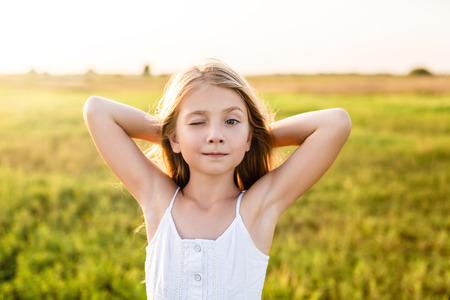 adorable little child winking at camera on green field under sunset rays Banque d'images