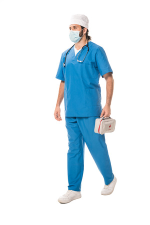 full length view of doctor in medical mask holding first aid kit and walking isolated on white