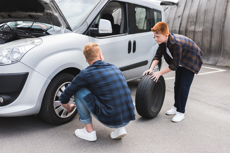 father and son changing tire in car with wheel wrench on weekend