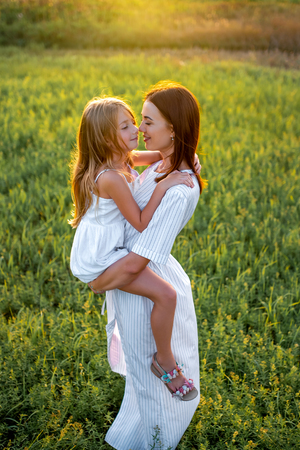 high angle view mother and daughter embracing in green meadow
