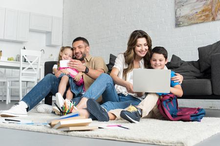 sorridente padre e figlia prendendo selfie sullo smartphone mentre madre e figlio utilizzano laptop insieme a casa Archivio Fotografico