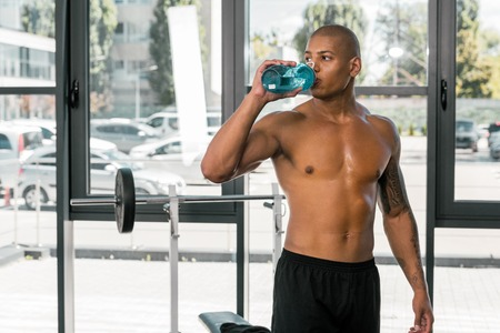 muscular bare-chested sportsman drinking water and looking away in gym