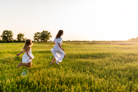 mother and daughter running in green meadow with sunset on background