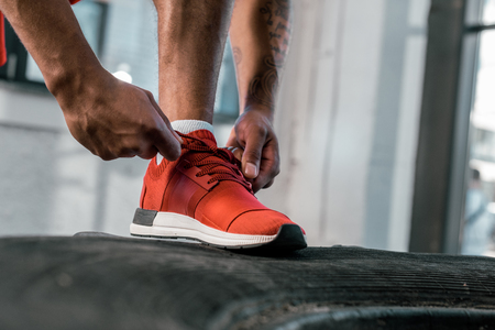 cropped image of sportsman tying laces of red sneakers at gym