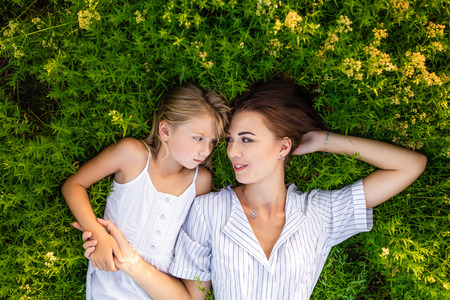 top view of mother and daughter relaxing while lying in flowery meadow and looking at each other Banque d'images - 109920761