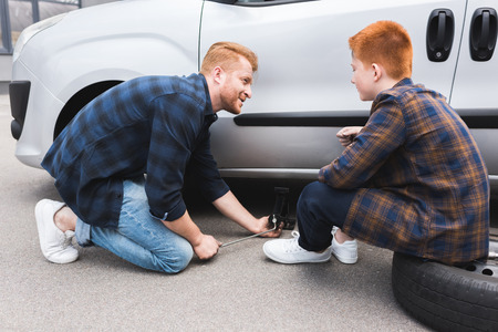 father lifting car with floor jack for changing tire, son looking at him