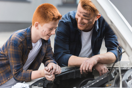 happy father and son repairing car with open hood