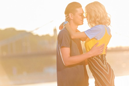 side view of young couple going to kiss on river beach during sunset