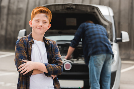 father repairing car with open hood, son looking at camera Stock Photo