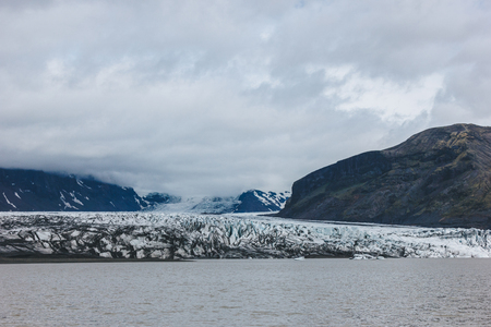 scenic view of glacier Skaftafellsjkull and snowy mountains against cloudy sky in Skaftafell National Park in Iceland
