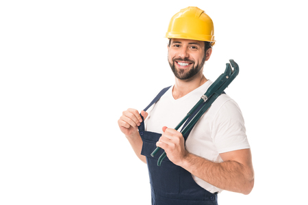 handsome happy workman holding adjustable wrench and smiling at camera isolated on white Stockfoto