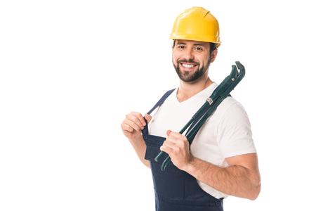 gutaussehender glücklicher Arbeiter, der verstellbaren Schraubenschlüssel hält und an Kamera lokalisiert auf Weiß lächelt
