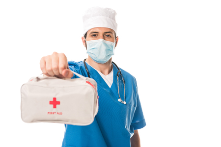 close-up view of doctor in medical mask holding first aid kit and looking at camera isolated on white 写真素材
