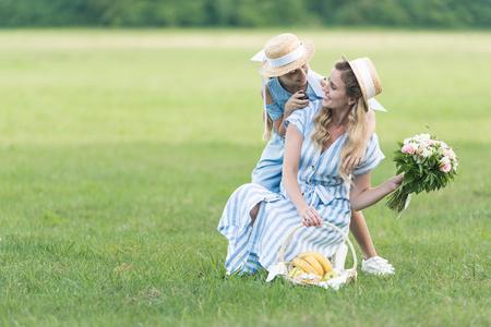 glückliche Eltern und Tochter, die Picknick mit Früchten und Blumenstrauß auf grünem Rasen haben