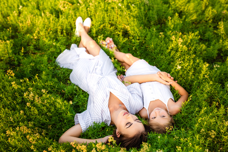 happy mother and daughter relaxing while lying in flowery meadow Banque d'images - 109923114