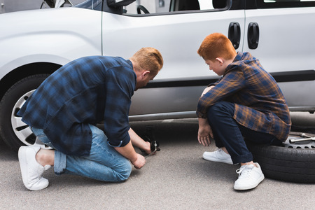 father lifting car with floor jack for changing tire, son sitting on tire Stok Fotoğraf