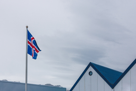 iceland flag and blue rooftop in front of cloudy sky Stock fotó