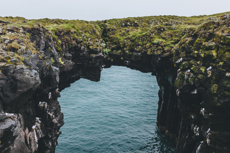 mossy rocky cliff in shape of arch with blue ocean on background in Arnarstapi, Iceland Stock Photo