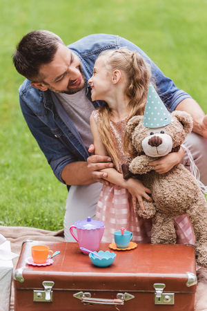 father and daughter with teddy bear playing tea party at lawn Stock Photo