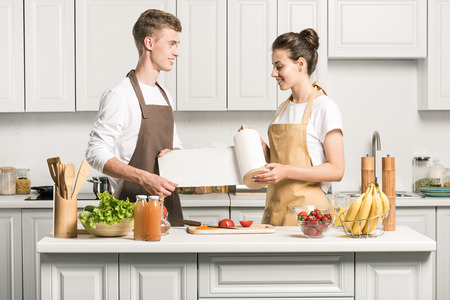 young couple cooking salad and holding paper towel in kitchen Banque d'images