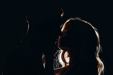 silhouettes of sensual heterosexual couple kissing in dark 스톡 콘텐츠