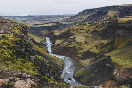 aerial view of curvy river streaming in green hills in Iceland on cloudy day