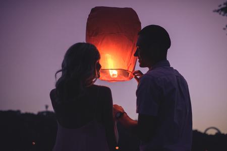 Siluetas de pareja lanzando sky lantern en la playa fluvial en la noche y mirando el uno al otro Foto de archivo
