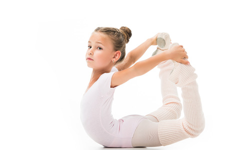 Schönes kleines Kind, das Gymnastikübungen lokalisiert auf weißem Hintergrund tut