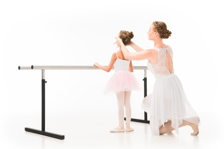 Rear view of adult female teacher in tutu helping little ballerina exercising at ballet barre stand isolated on white background Zdjęcie Seryjne