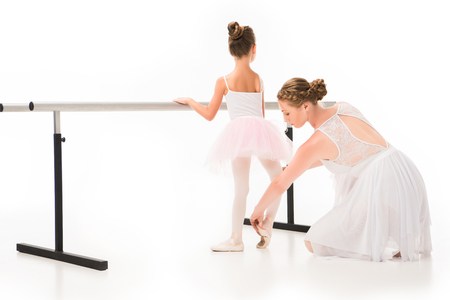 Rear view of female teacher in tutu checking pointer shoes of little ballerina exercising at ballet barre stand isolated on white background Zdjęcie Seryjne
