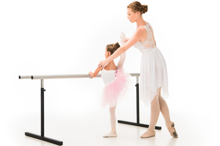 Side view of female teacher in tutu helping little ballerina practicing at ballet barre stand isolated on white background
