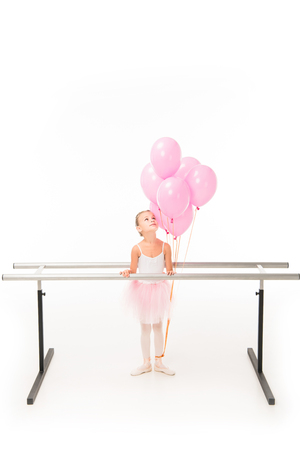 Little ballerina in tutu standing at ballet barre stand and looking up at pink balloons isolated on white background Imagens