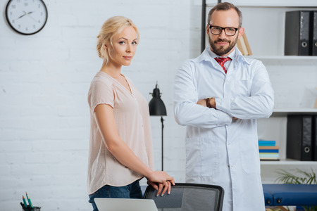 Portrait of doctor in white coat and female patient looking at camera in clinic Фото со стока