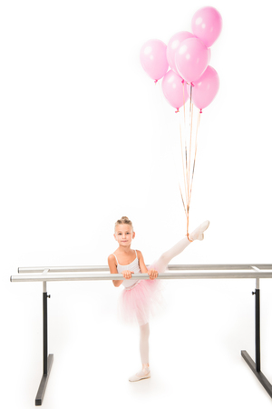 Adorable little ballerina in tutu practicing with pink balloons wrapped over her at ballet barre stand isolated on white background