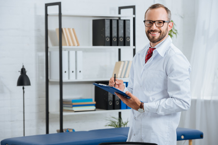 Portrait of smiling male chiropractor in white coat and eyeglasses with notepad in hospital