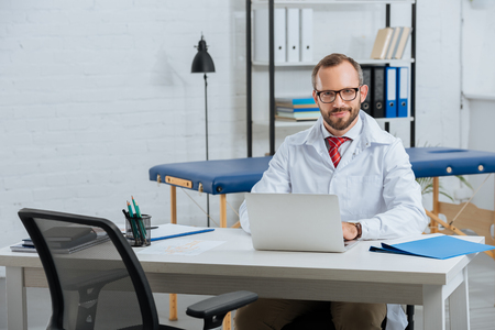 Portrait of smiling male chiropractor in white coat at workplace with laptop in hospital Фото со стока
