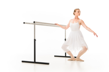 Elegant ballerina in tutu and pointer shoes practicing at ballet barre stand isolated on white background Stock Photo