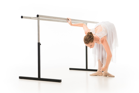 Ballerina in tutu and pointer shoes practicing at ballet barre stand isolated on white background 写真素材