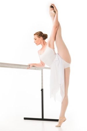 Adult ballerina in tutu and pointer shoes stretching at ballet barre stand isolated on white background Zdjęcie Seryjne