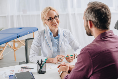 Smiling physiotherapist in white coat looking at patient during appointment in clinic