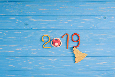 Top view of 2019 symbol, pig and christmas tree on blue wooden surface
