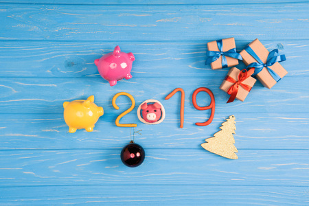 Top view of 2019 symbol with pink and yellow piggy banks and christmas presents on blue wooden surface