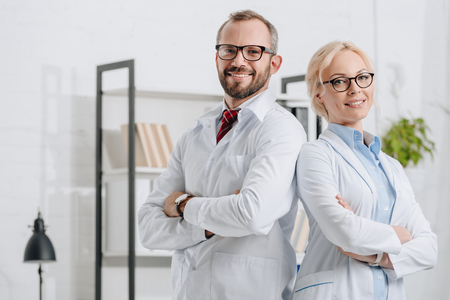 Portrait of smiling physiotherapists in white coats looking at camera in clinic