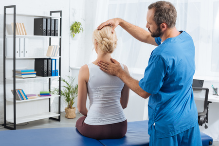 Physiotherapist doing massage to woman on massage table in hospital