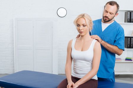 Physiotherapist massaging woman shoulders on massage table in hospital