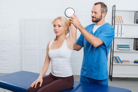 Quiropráctico sonriente estirando el brazo de la mujer en la mesa de masajes en la clínica Foto de archivo