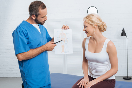 Physiotherapist showing human body scheme to smiling woman on massage table in hospital Imagens