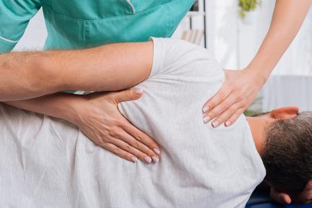 Toma recortada del quiropráctico masajeando la espalda del paciente en la mesa de masaje en el hospital