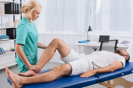 Female massage therapist doing leg massage to patient on massage table in clinic